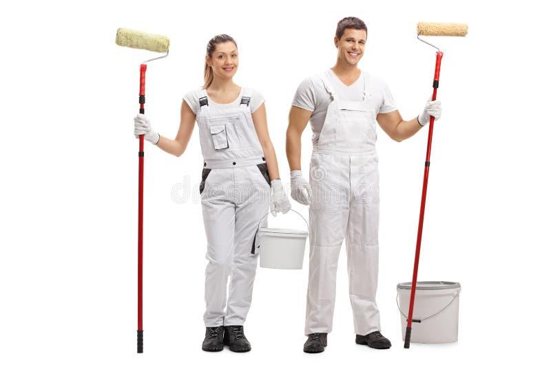 女性和一位男性画家有桶和漆滚筒的 库存图片