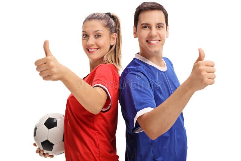 女性和举行他们的赞许的一位男性足球运动员 库存照片