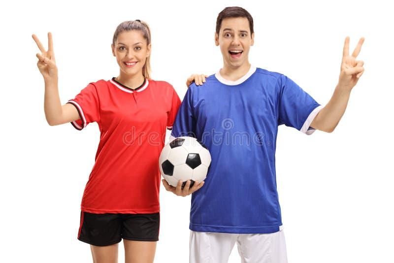 女性和做胜利标志的一位男性足球运动员 免版税库存照片