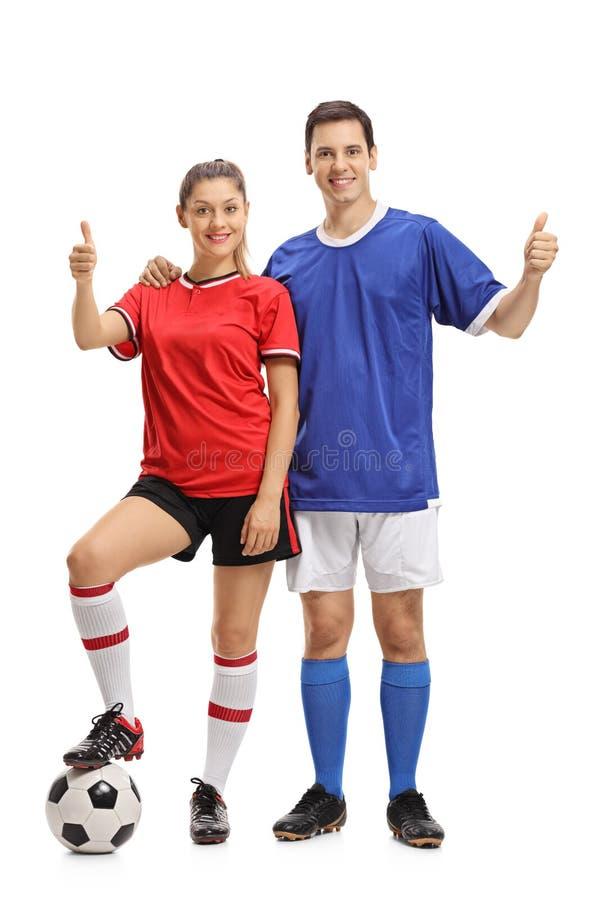 女性和做赞许姿态的男性足球运动员 库存图片