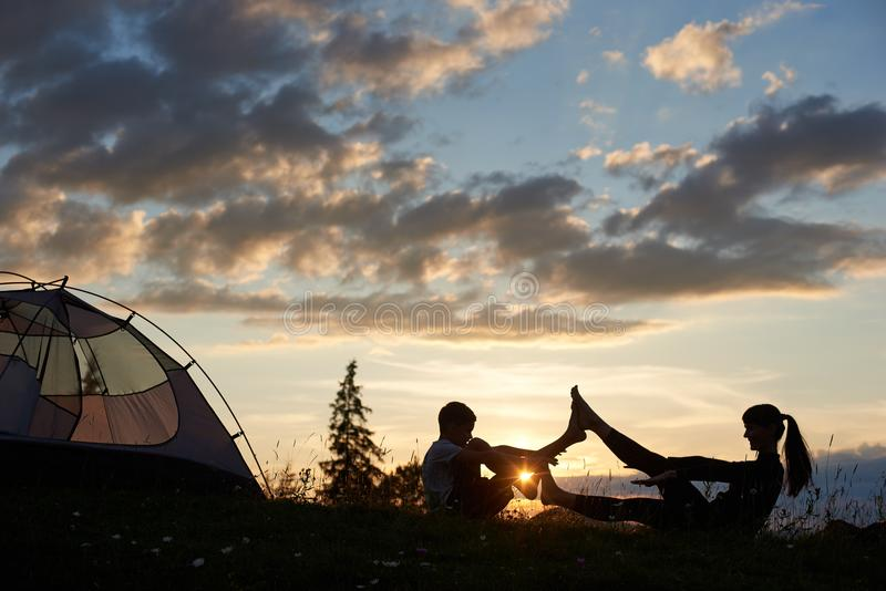 女性和男孩剪影坐在瑜伽姿势的草在破晓在帐篷附近 图库摄影