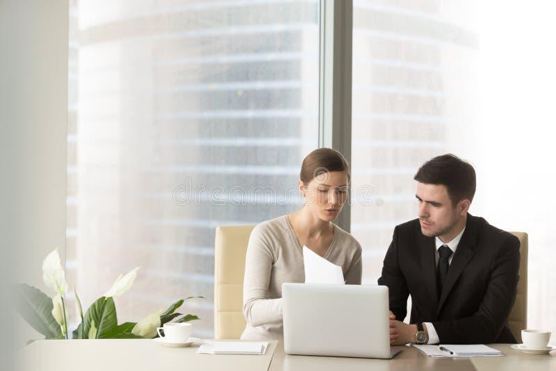 女性和男性同事与文件一起使用 库存照片