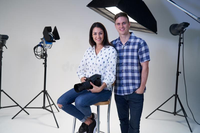 女性和男性摄影师画象在照片写真的演播室与照相机和照明设备 图库摄影