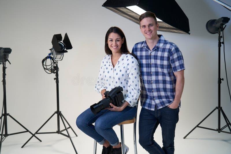 女性和男性摄影师画象在照片写真的演播室与照相机和照明设备 库存照片