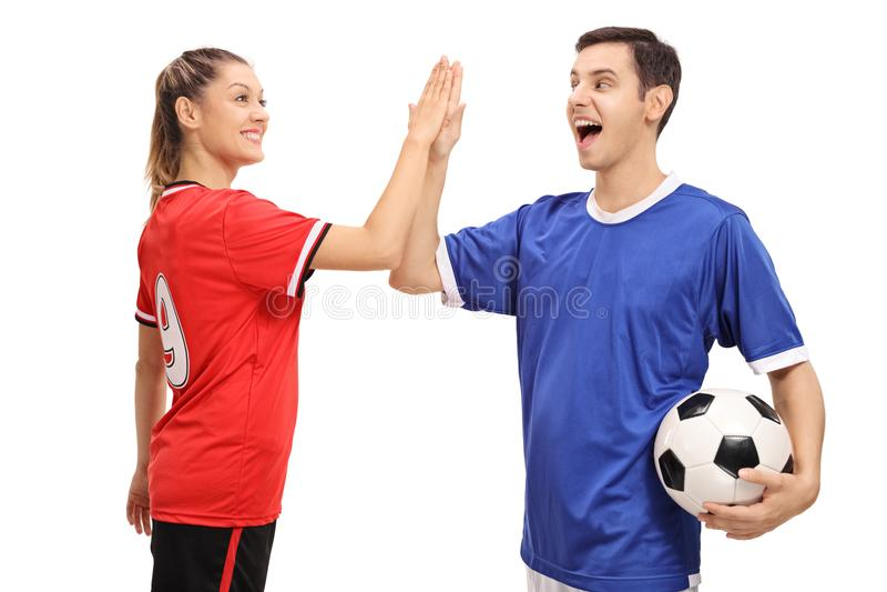 女性和高fiving一位男性的足球运动员 免版税图库摄影