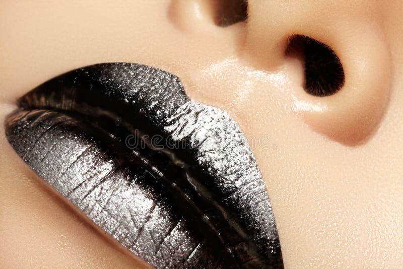 女性嘴宏观特写镜头  有银色闪烁构成的性感的黑光泽嘴唇 万圣夜样式构成 黑暗的唇膏 库存图片