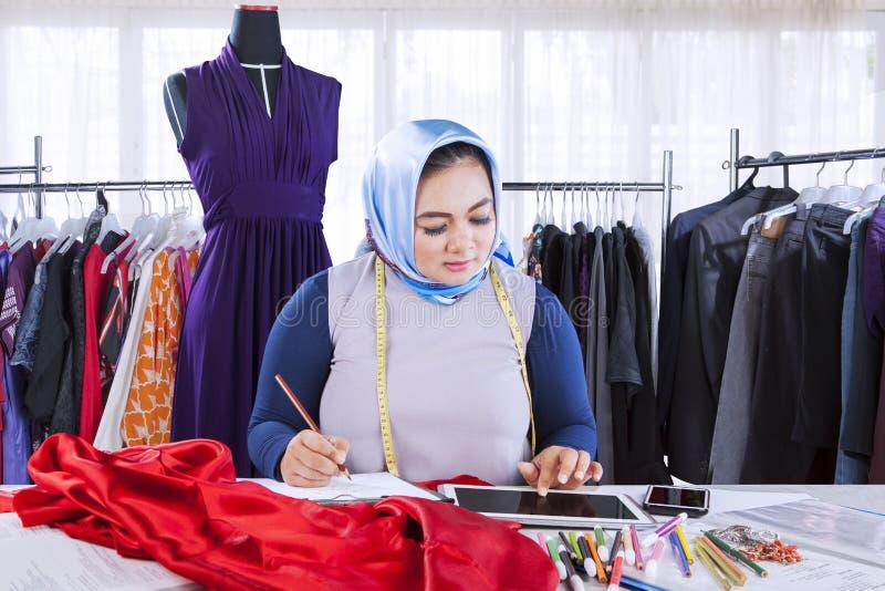 女性回教时装设计师与数字式片剂一起使用 免版税库存图片