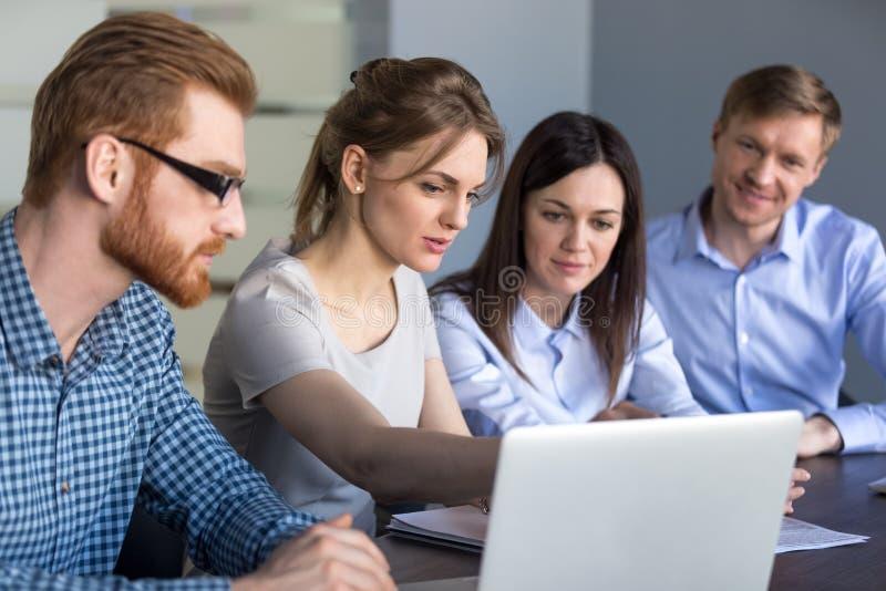 女性团队负责人解释项目战略在膝上型计算机对colleag 免版税库存照片