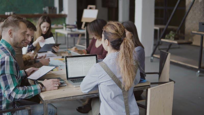 女性团队负责人给创造性的企业队带来文件 见面在现代办公室的混合的族种人 免版税库存图片