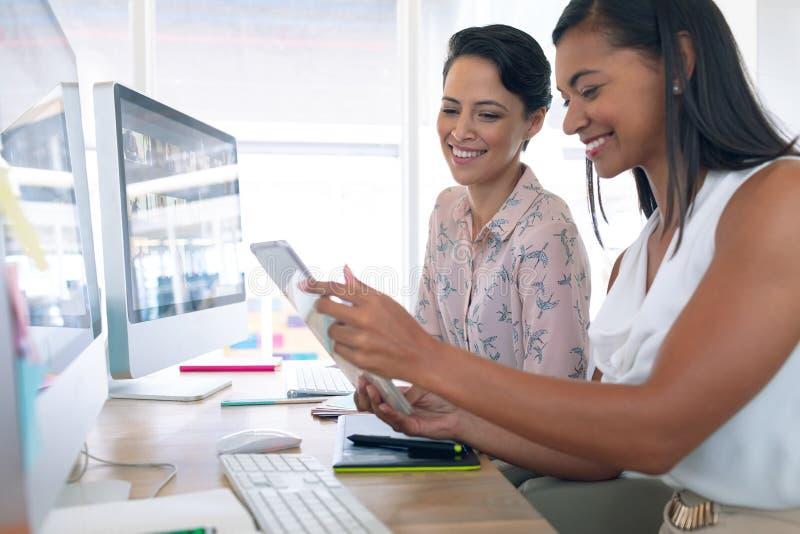 女性图表设计师谈论在数字片剂在书桌在一个现代办公室 库存图片
