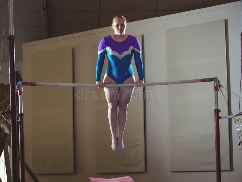 女性在单杠的体操运动员实践的体操 库存图片