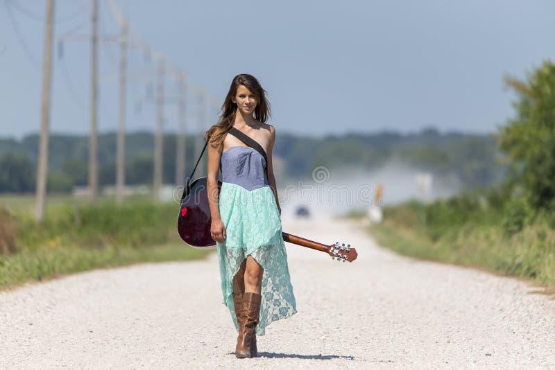 女性在土路搭车 图库摄影