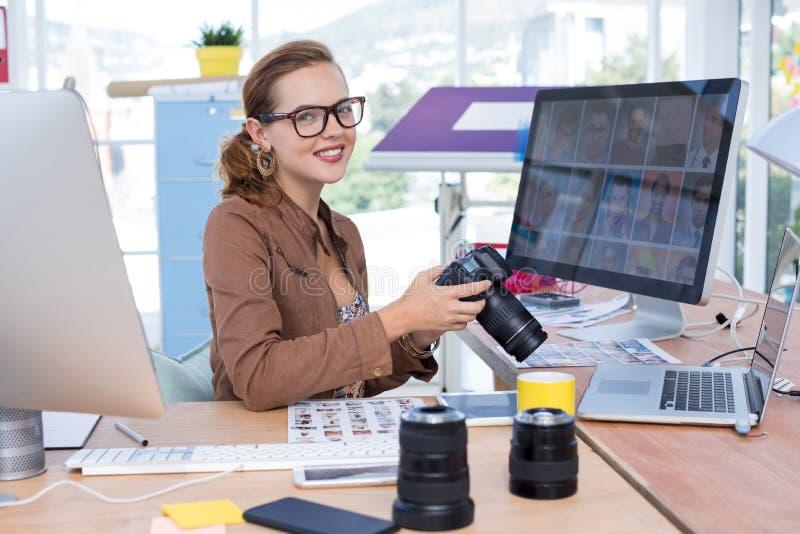 女性在她的书桌的执行委员回顾的被夺取的照片在办公室 免版税库存图片
