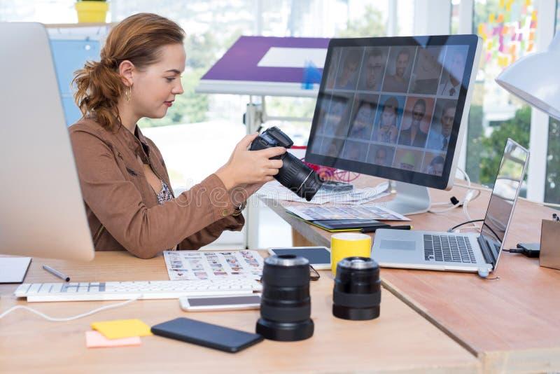 女性在她的书桌的执行委员回顾的被夺取的照片 免版税库存图片