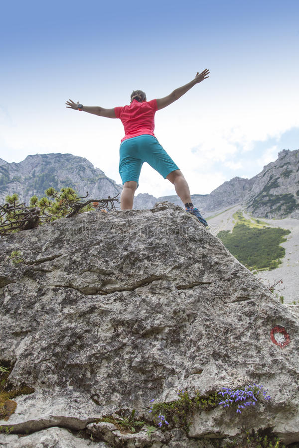 女性在岩石的远足者上升的手高在山 库存图片