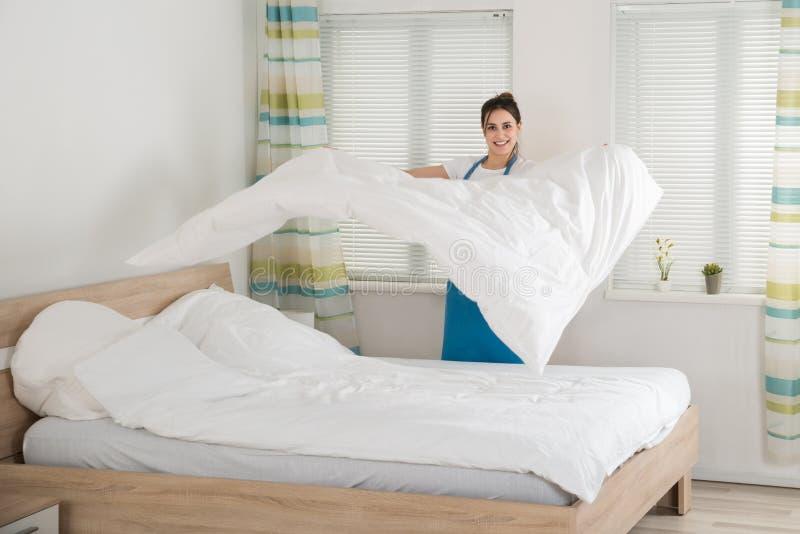女性在床上的管家改变的床单 免版税库存照片