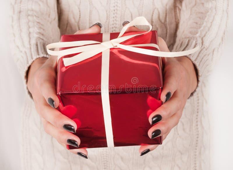 女性在手上的拿着红色礼物盒有黑钉子和毛线衣的 免版税库存照片
