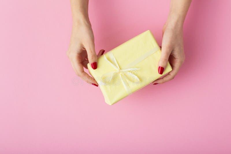 女性在手,妇女上拿着一个礼物有礼物盒的在在桃红色背景,顶视图,概念的装饰纸包裹的手上 免版税库存照片