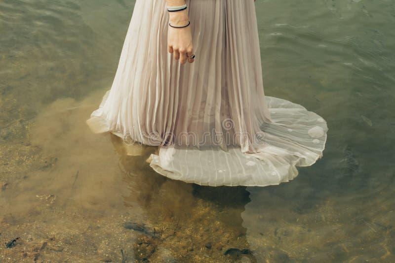 女性在水中佩带一个长的褂子礼服身分 免版税库存照片