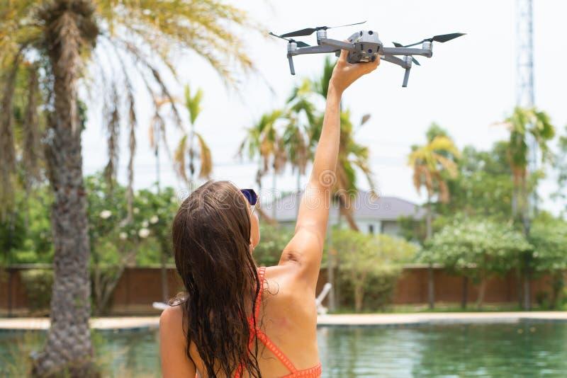 女性在游泳场和棕榈树附近发射飞行的一条寄生虫,您能采取照片和录影, 免版税库存照片