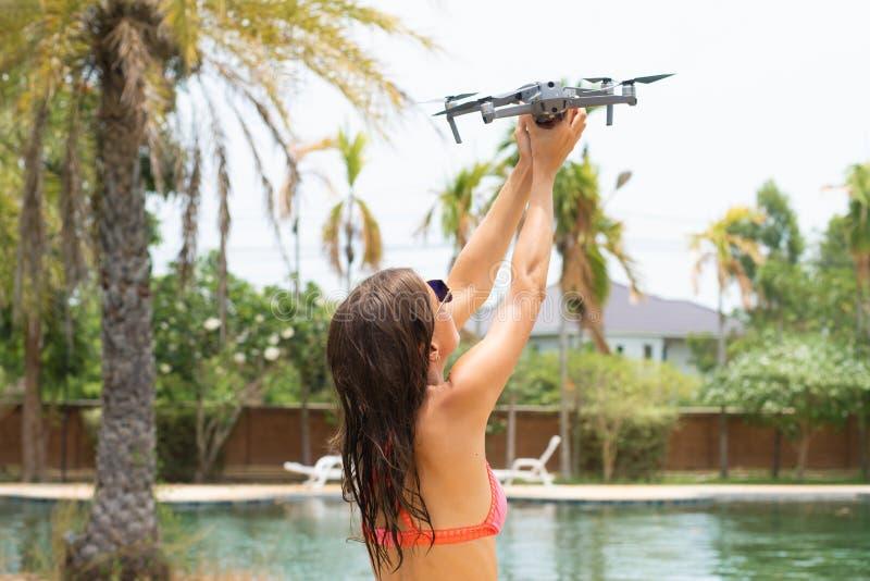 女性在游泳场和棕榈树附近发射飞行的一条寄生虫,您能采取照片和录影, 免版税库存图片