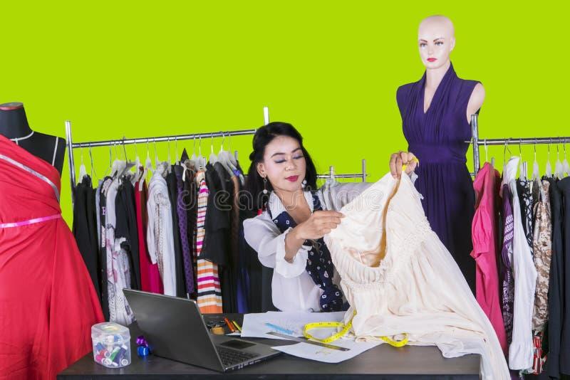 女性在演播室的时尚编辑测量的织品 免版税库存图片