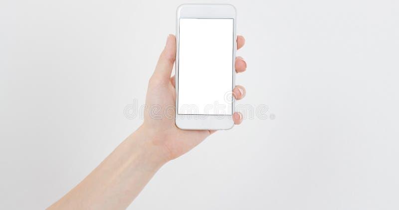 女性在白色隔绝的手举行手机,妇女有空的显示的,黑屏藏品电话,接触 免版税库存照片