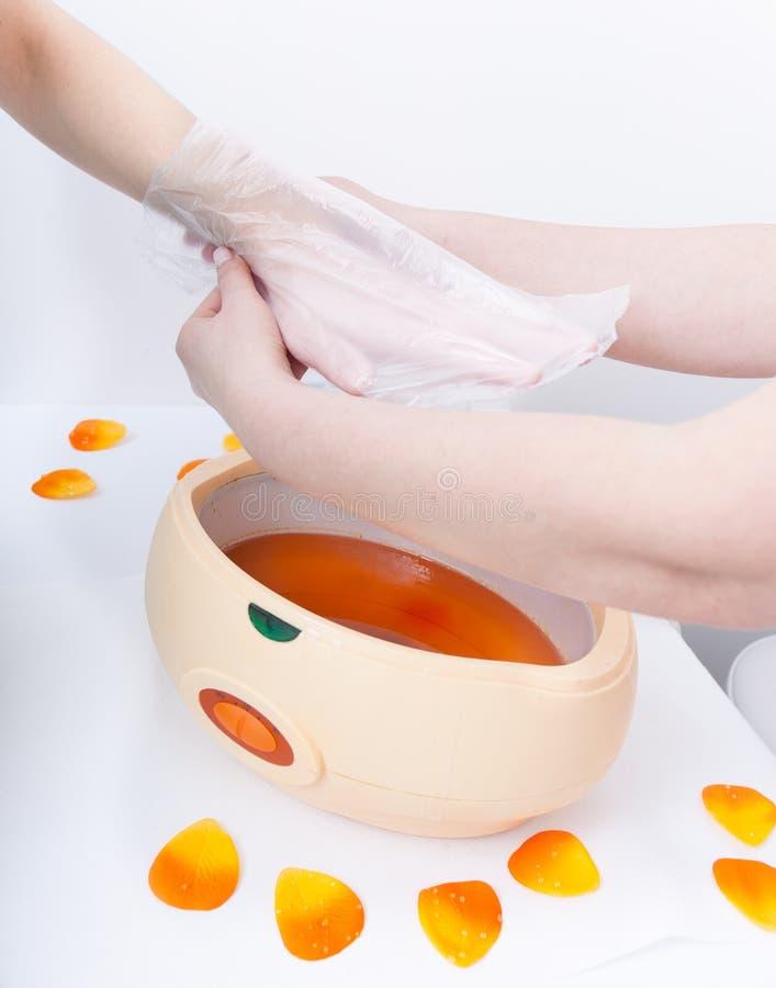 女性在碗的手橙色parrafin蜡 修指甲秀丽温泉沙龙 免版税库存照片