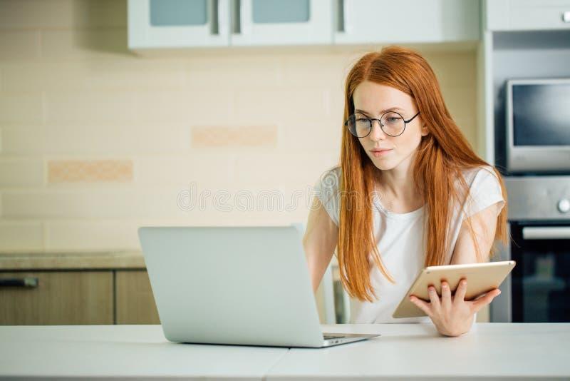 女性在网上与数字式片剂和膝上型计算机一起使用,当坐在桌上时 免版税图库摄影