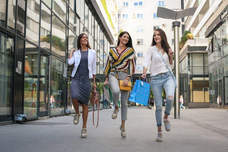 女性在购物以后的朋友走的街道 免版税库存照片