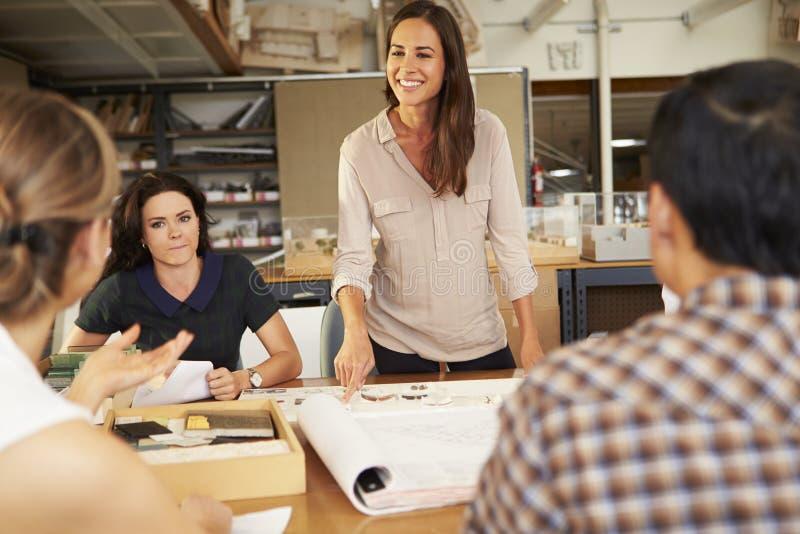 女性坐在表上的建筑师上司主导的会议  免版税库存图片
