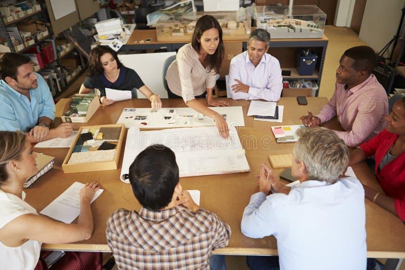女性坐在表上的建筑师上司主导的会议  库存图片