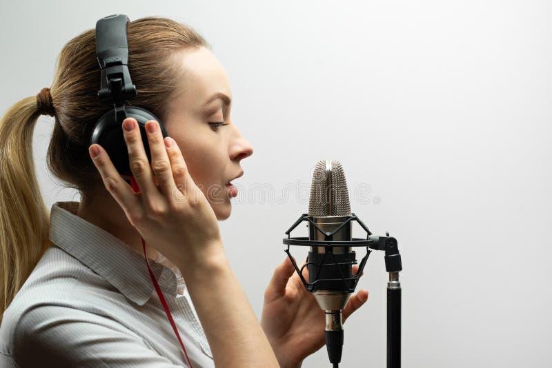 女性声音录音 有话筒和耳机的少女在录音室 录音声音,博客作者,读书文本, 免版税库存照片