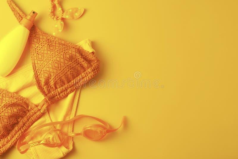 女性夏天比基尼泳装泳装和辅助部件,被定调子的黄色 r 库存照片