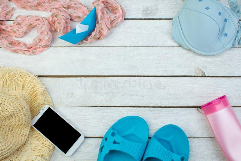女性夏天海滩辅助部件帽子、泳装、遮光剂、太阳镜、帽子、电话、触发器和耳机平展放置,顶面 免版税库存照片