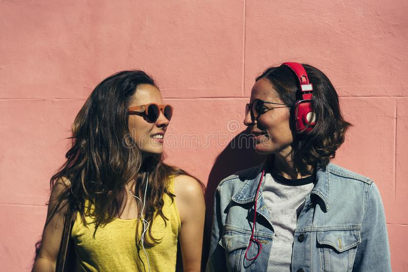 女性夫妇听的音乐和一起消费时间在桃红色墙壁 一个对年轻女同性恋的妇女夫妇,概念的同性 免版税库存图片