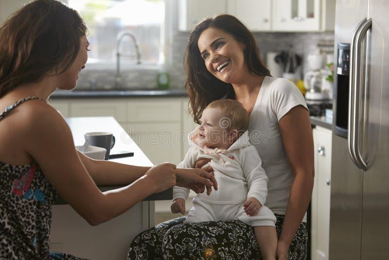 女性夫妇在有女婴的厨房里坐膝盖 免版税库存照片
