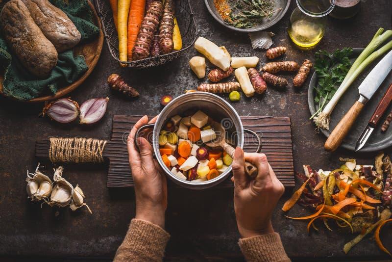 女性妇女递拿着有切成小方块的五颜六色的菜和一把匙子的平底锅在与烹调ingredie的素食主义者的土气厨房用桌上 免版税库存照片