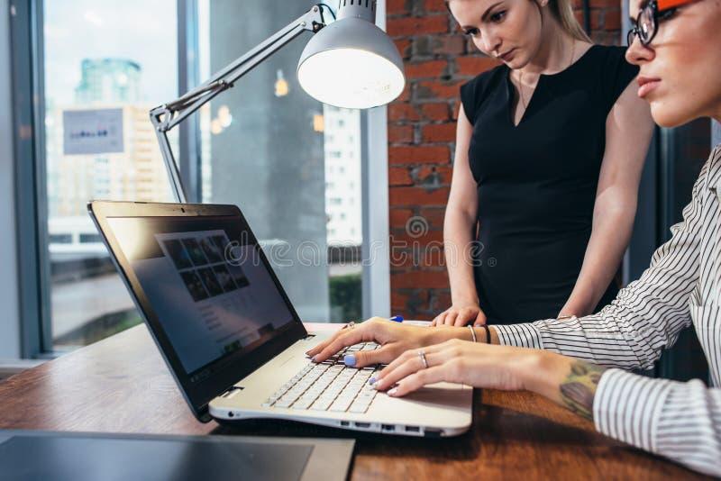 女性室内设计师与顾客观看的图片一起使用使用坐在现代演播室的膝上型计算机 库存图片