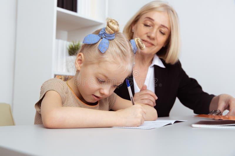 女性家庭教师帮助的女孩的图片 老师和学生概念 免版税库存照片