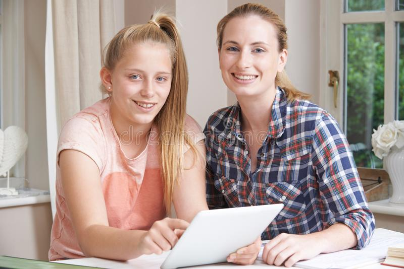女性家庭有研究的家庭教师帮助的女孩使用数字式片剂 免版税库存照片