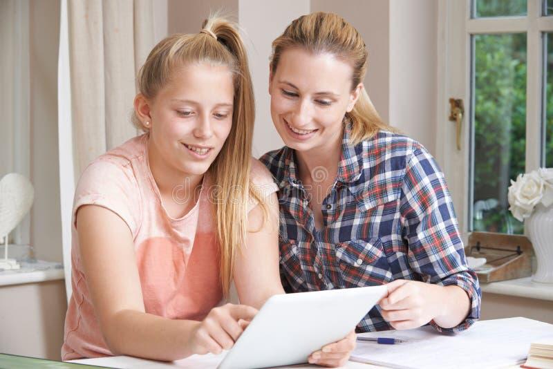 女性家庭有研究的家庭教师帮助的女孩使用数字式片剂 库存图片