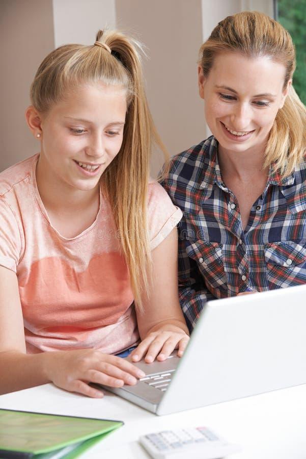 女性家庭有研究的家庭教师帮助的女孩使用膝上型计算机 库存照片