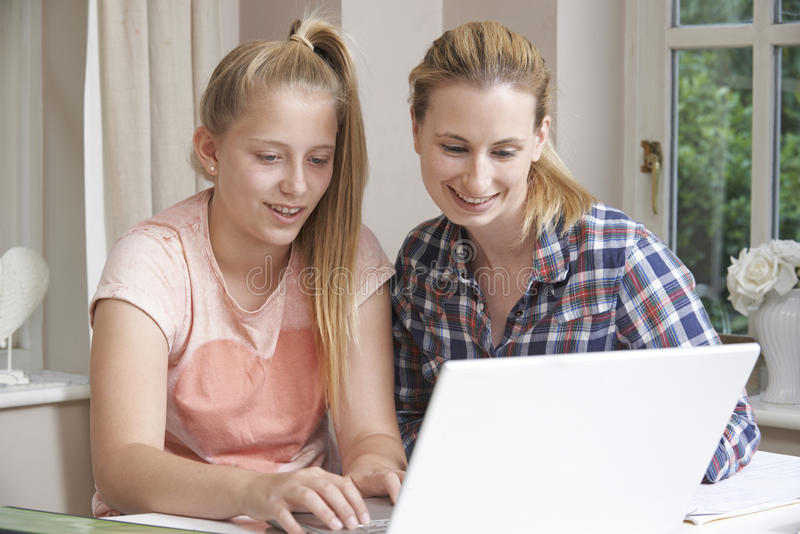 女性家庭有研究的家庭教师帮助的女孩使用膝上型计算机 库存图片