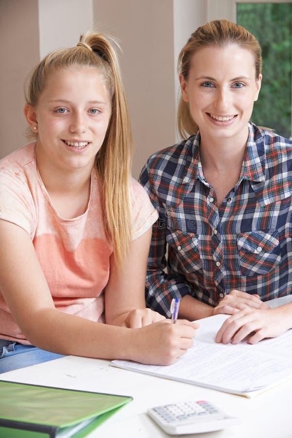 女性家庭有研究的家庭教师帮助的女孩 库存图片