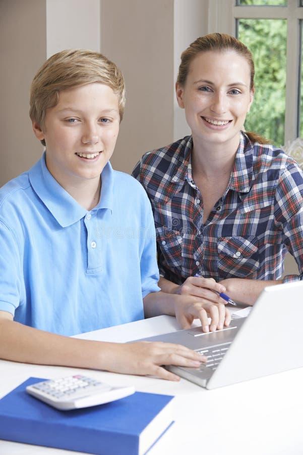 女性家庭有研究的家庭教师帮助的男孩画象使用膝部 库存照片
