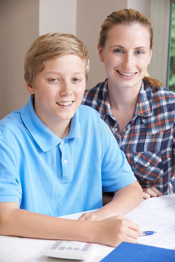 女性家庭有研究的家庭教师帮助的男孩画象  免版税库存照片