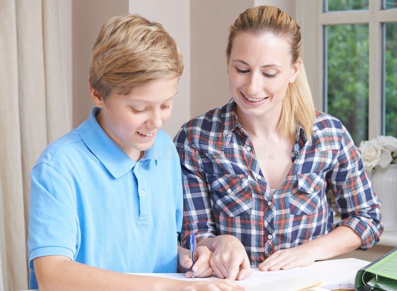 女性家庭有研究的家庭教师帮助的男孩 库存图片