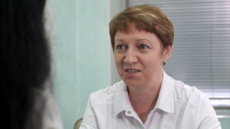 女性对妇女患者的医生震动的谈话 免版税图库摄影