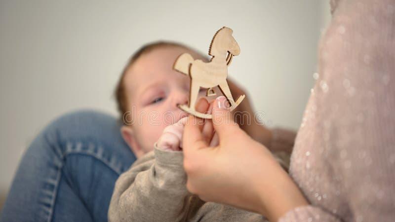 女性对婴儿婴孩的陈列木马形象,早期的儿童发育 免版税库存照片